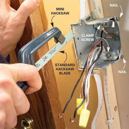 <b>Photo 4: Cut the box loose</b></br> Slide a sharp hacksaw blade between the box and the stud and cut off the nails. Loosen the box clamp screws, pull out the box and remove the wires.