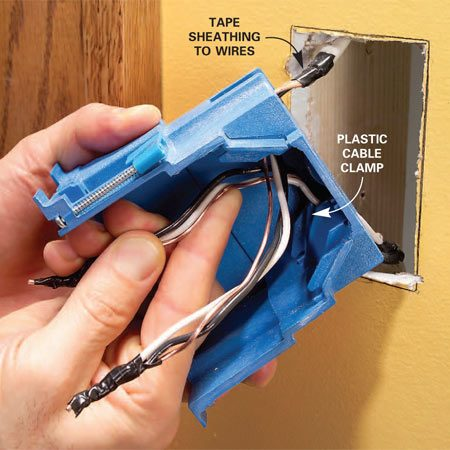 <b>Photo 7: Insert wires in box</b></br> Tape the cable sheathing tightly to the wires. Then feed wires into the new box through the cable clamps. Work them in gradually while pushing the box into the wall.