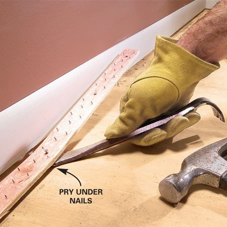 <b>Photo 3: Remove the old tack strips</b></br> Pry out as many 4 ft. sections of tack strip with a pry bar as needed to clear the new built-in. Then discard them.