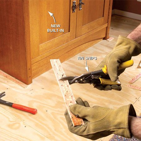 <b>Photo 4: Cut new tack strips</b></br> Cut new tack strips to length with a pair of tin snips. Wear gloves to protect your hands from the needle-sharp tacks.