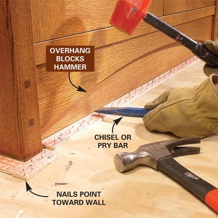 <b>Photo 5: Nail down the new tack strips</b></br> Space the tack strips about 1/2 in. away from the baseboards and nail them into place with the gripping nails pointing toward the walls. Use a cold chisel or pry bar and mallet to sink nails under toe-kicks.