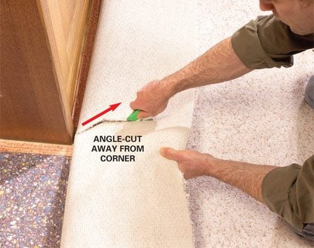<b>Photo 7: Cut the carpet oversize</b></br> Mark the carpet at outside corners and cut angled clearance cuts with a utility knife. Then trim off most of the excess carpet, leaving about 3 in. extra along each side.
