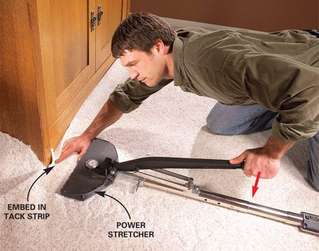 <b>Photo 8: Stretch and embed the carpet</b></br> Plant the power stretcher against the opposite baseboard and add extension sections until the gripping head is about 6 in. away from the wall. Push down on the lever and embed the carpet backing on the tack strips with your hand. Follow the sequence below.