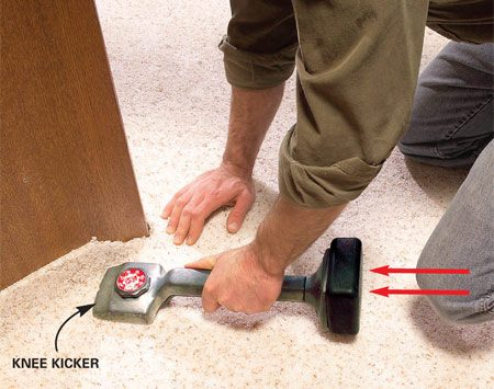 "<b>Photo 9: Kick tight areas</b></br> Stretch any remaining tight areas with the knee kicker. Rest the teeth about 6 in. back from the wall or built-in and ""kick"" with the spot above your kneecap. Then embed the carpet with your hand."