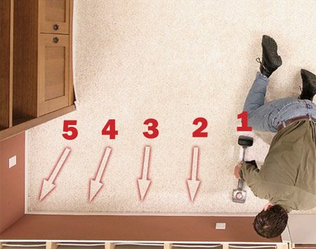 <b>Photo 9B: Knee-kick the first side</b></br> Stretch the carpet against the baseboard with the knee kicker and embed it into the tack strip. If it's too hard to stretch with the knee kicker, use the power stretcher.