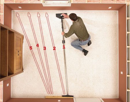 <b>Photo 9C: Stretch the opposite side</b></br> Stretch the opposite side of the room with the power stretcher. Start stretching beginning about a foot or so behind the point where the carpet was rolled back.