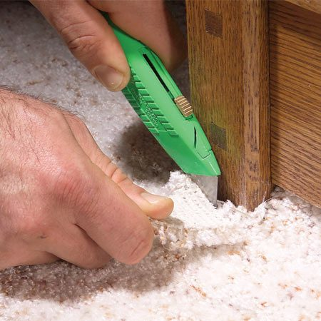<b>Photo 11: Trim tight areas with a utility knife</b></br> Use a utility knife to finish the cuts in corners and to trim around projections and other tight areas. Cut from the backside, leaving the carpet about 1/8 in. overlong to tuck tightly against the built-in.