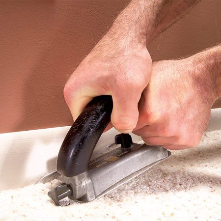 <b>Photo 12: Embed the edges</b></br> Embed the carpet edge firmly in the tack strip and under baseboards by forcing the front edge of the carpet cutter into the carpet and dragging it along the wall.