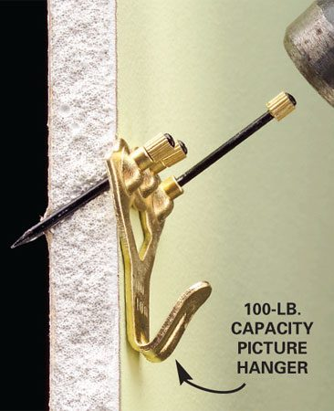 <b>Photo 1: Drive the nails</b></br> Slide the small nails (included) through the angled hole and tap them into the wall with a hammer. To remove the hanger, grab the end of the nail with pliers and twist it out.