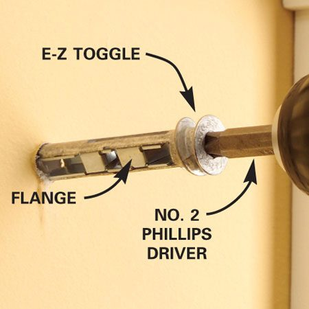 <b>Photo 1: Drive the toggle</b></br> Mark the mounting holes and drive an E-Z Toggle in at each mark. Slow down as soon as the threads engage in the drywall. Slowly tighten the toggle until it's snug and nearly flush.
