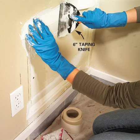 <b>Step 3: Tape the joints</b></br> Photo 3: Lay a 1/8-in.-thick bed of drywall compound over the joints and press paper tape into the compound with a flexible 6-in. knife. Immediately apply a thin layer of compound on top of the tape. Allow to dry.