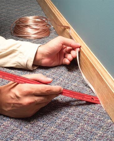 <b>Easy wire hiding</b></br> Use a stir stick is a great tool for tucking the wire between the carpet and baseboard.