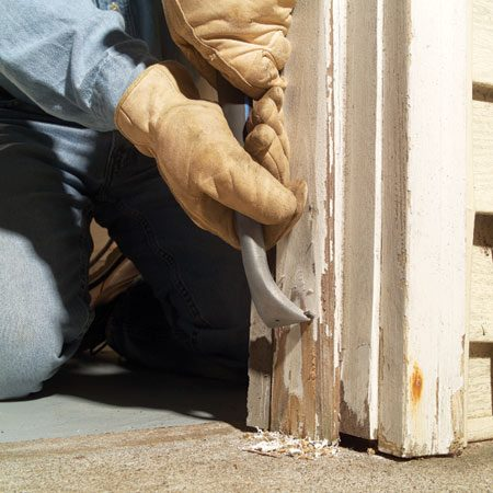 <b>Photo 1: Remove loose paint</b><br/>Scrape away all the paint within 16 in. of the concrete. Scrapers with replaceable carbide blades work best. Also dig any old caulk out of joints.