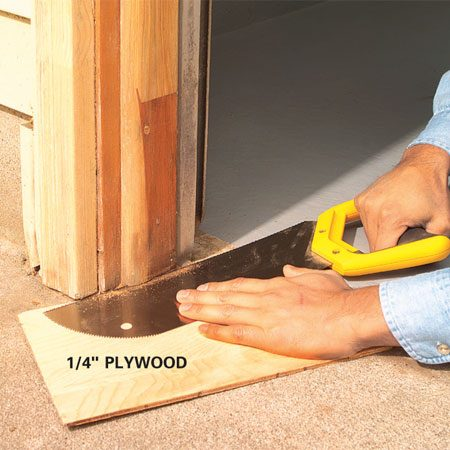<b>Photo 3: Create a gap between trim and concrete</b></br> Undercut the trim to create a gap between the wood and concrete. Use a scrap of 1/4-in. plywood for a saw guide.