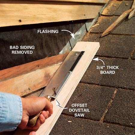 <b>Photo 4: Cut siding back from the roof</b></br> Cut the siding back from the shingles using a 3/4-in. thick board to guide your saw. Be careful not to cut into the metal flashing.