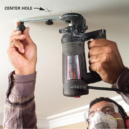 <b>Photo 1: Center the pin</b></br> Punch a hole with a drywall nail at the center mark. Align the pin with the center hole, and with the spiral saw running, pivot the bit into the drywall.