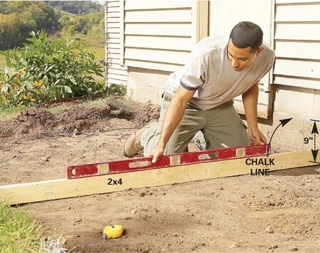 <b>Photo 2: Excavate</b></br> Dig 6 to 8 in. of soil from the sidewalk area. Then snap a chalk line on the house to represent the top of the sidewalk. Excavate to a depth of 9 in. below the chalk line with a slight slope away from the house. Caution: Call the local utilities or 811 to locate any buried lines in the vicinity before digging.