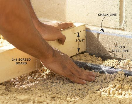 <b>Photo 5: Add a final layer</b></br> Spread a final loose layer of gravel about 1 in. thick. Set a 10-ft. x 1-in. outside diameter steel pipe in the gravel and level it 2-3/4 in. below the chalk line.