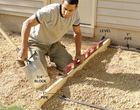 <b>Photo 6: Use pipes to guide a level screed</b></br> Set a second pipe parallel to the first near the outer edge and level it about 1 in. below the first pipe, using a straight 2x4 and a 4-ft. level with a 3/4-in. scrap block under one end.