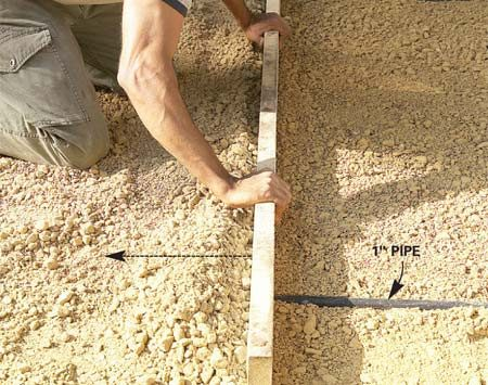 <b>Photo 7: Level the gravel</b></br> Pull a 2x4 along the pipes to flatten the loose gravel and fill in low spots. Remove the pipes and fill in the troughs with gravel. Then compact.