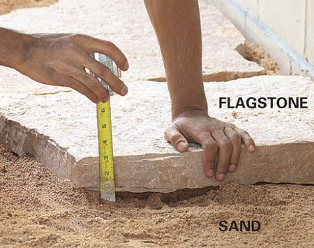 <b>Photo 8: Begin setting flagstone</b></br> Dump a few wheelbarrows of sand on the gravel and set the flagstone 3 in. above the gravel layer. Adjust the corners, adding and removing sand as needed.