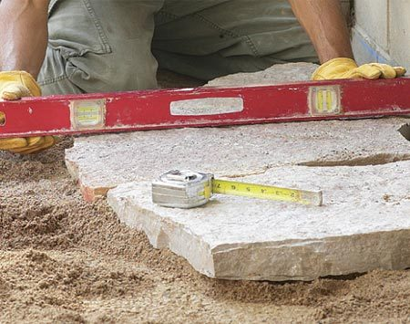 <b>Photo 9: Maintain a slight slope</b></br> Check the surface of the stone with your level so it maintains a slight slope away from the house. Raise or lower edges with the sand.