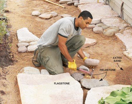 <b>Photo 10: Fill in with the fieldstone</b></br> Set the fieldstone tightly in the niches of the flagstone. For thicker stone, scrape gravel away with the claw of a hammer. Stand back to check the overall appearance. Change or reset stones that look out of place.