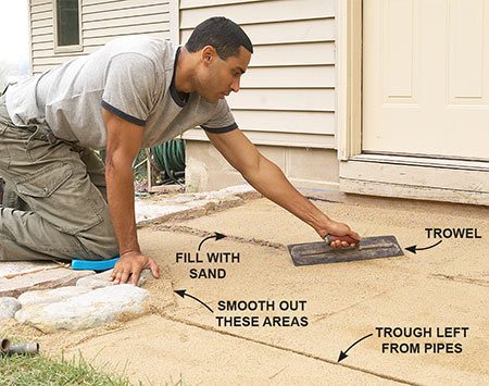 <b>Photo 12: Smooth the sand bed</b></br> Remove the pipes, fill the troughs with sand and smooth with a trowel. Also smooth the areas around the stones with your trowel.