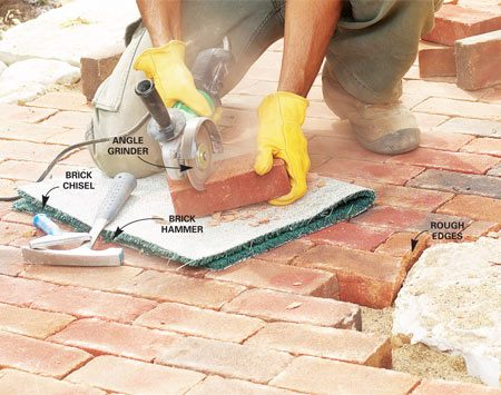 <b>Photo 18: Cut the brick</b></br> Score a 1/2-in. deep groove in the underside of the brick with an angle grinder. Then set the brick on scrap carpet, position the brick chisel in the cut and rap it with the hammer to break it, leaving a rough edge.