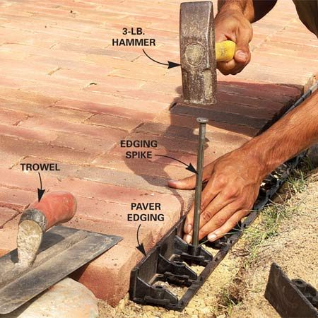 <b>Photo 19: Attach paver edging</b></br> Cut away the sand along the edge of the sidewalk down to the gravel with the edge of a trowel. Fasten paver edging along the perimeter of the walk with spikes driven every 12 in.