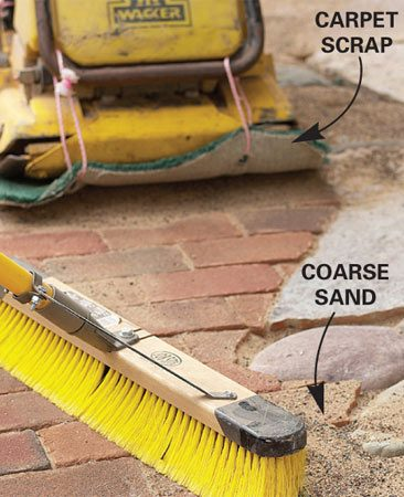 <b>Photo 21: Fill the joints with sand</b></br> Sweep dry sand into the brick joints. Run the compactor over the brick and sweep in more sand until the joints are completely full.