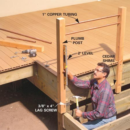 <b>Photo 14: Attach the posts</b></br> Drill 1-in. countersink holes and 3/8-in. clearance holes in the posts for the lag screws. Cut the copper tubes and set them in their holes. Plumb the posts with shims and attach them with lag screws.