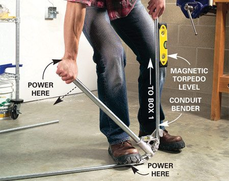 <b>Photo 5: Start the bend</b></br> Place the conduit in the bender with the mark directly in line with the arrow (see next photo). Step on the conduit bender and push down on the handle until the conduit forms a 90-degree angle and is level.