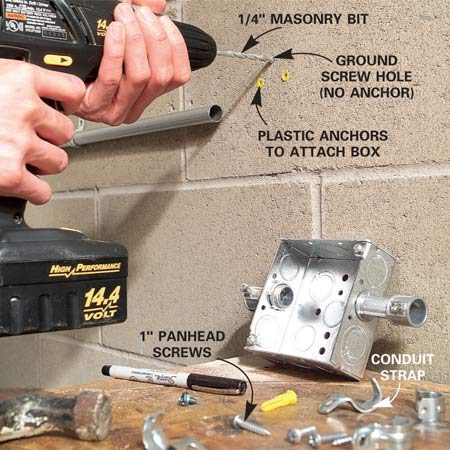 <b>Photo 10: Drill the holes</b></br> Reposition the conduit and Box 2 and mark hole locations for plastic anchors. Drill the holes, then mount the box and conduit straps with panhead screws.