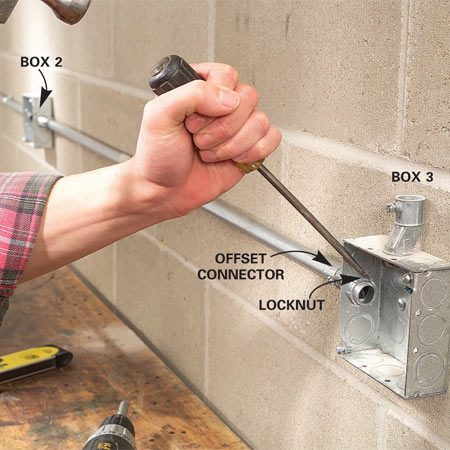 <b>Photo 11: Tighten the locknuts</b></br> Position Box 3, measure the distance to Box 2 and cut the conduit to fit. Repeat steps 9 and 10 to mount them. Now tighten all offset connector locknuts with a hammer and screwdriver.