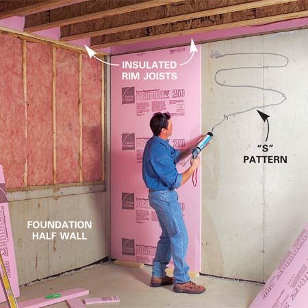 <b>Photo 1: Install insulation</b></br> Cut 3/4-in. extruded polystyrene insulation to fit against the rim joists. Spread a 1/4-in. bead of adhesive on masonry walls and press the sheets into place.