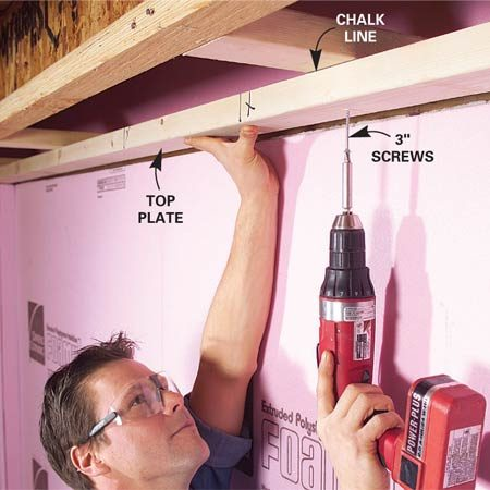 <b>Photo 6: Install the top plate</b></br> Plumb from the edge of the bottom plate to the blocking with a straight 2x4 and level. Snap a chalk lin and screw the top plate to the blocking with 3-in. screws.