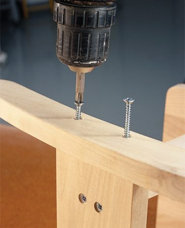 <b>Photo 3: Drive in screws</b></br> Place the screws in the holes of the top piece so their points project slightly through the bottom. Align the points with the pilot holes for proper positioning, then drive the screws tight. Wipe off glue that squeezes out.