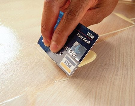 <b>Use a glue spreader</b></br> While a notched glue spreader is the most effective and neatest tool for spreading glue on a flat surface, you can use an old credit card in a pinch. Draw it lightly over the glue to leave a thin film. For spreading glue on smaller or curved surfaces, you can buy stiff-bristled 1/4-in. throw-away brushes in the home center plumbing department. Or use the time-honored finger; just make sure you wipe your finger clean before you mess up that masterpiece you're building.