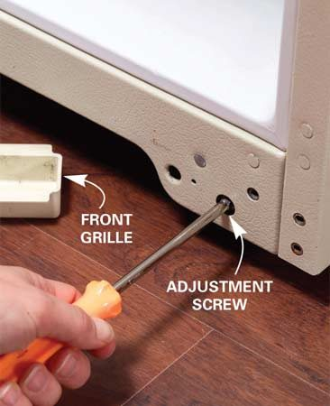 <b>Photo 8: Use the adjustment screws </b></br> Pull off the front cover grille to level or tilt the fridge. Turn adjustment screws to raise or lower the front corners of the fridge.