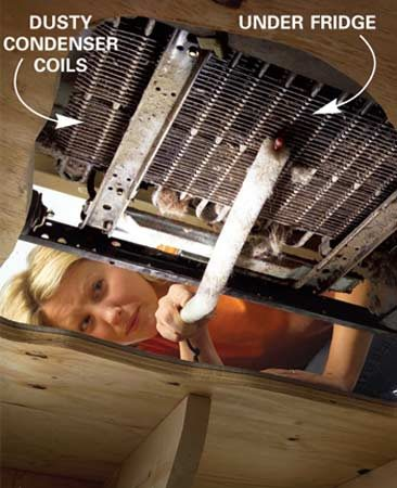<b>Photo 12: Clean the coils</b></br> Clean the coils so air can flow through them. Pull dust and fur balls from beneath and between coils with a long brush.