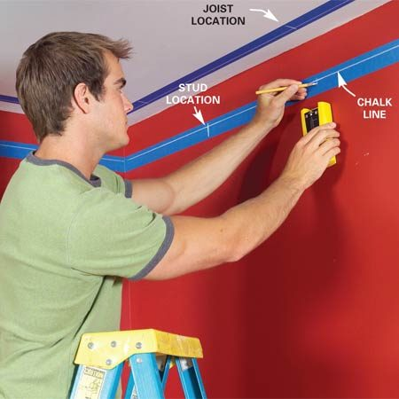 <b>Photo 2: Mark the walls and ceiling</b></br> Run masking tape around the walls and ceiling so that about 1/2 in. of the tape will be covered by the rail trim. Mark the rail positions with a chalk line. Locate studs and ceiling joists.