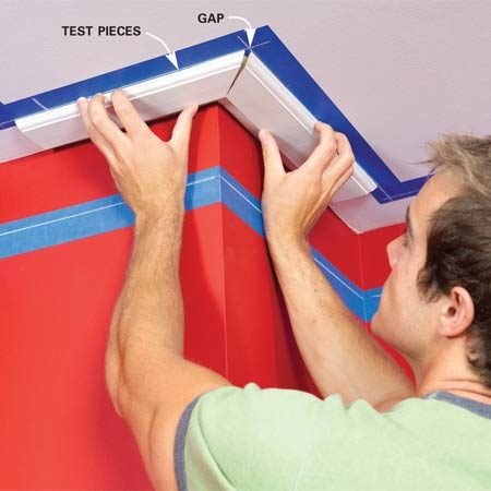 <b>Photo 3: Test the miter angle</b></br> Find the right miter angle for the ceiling rails at inside and outside corners. Miter scraps to 45 degrees and hold them in place along the chalk lines. If there's a gap, adjust your saw's angle and cut again until they fit tight.