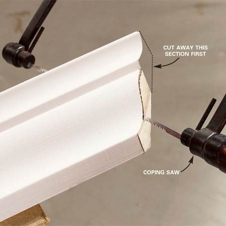 <b>Photo 12: Coping the molding</b></br> Cut a cope by following the edge left by the miter cut. Hold the saw at an angle to undercut behind the face of the molding. With many moldings, you have to cut away one section to get at another.