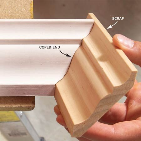 <b>Photo 13: Test-fit the molding</b></br> Test-fit the coped end using a scrap. Perfect the cut with a rasp. If you need to remove lots of wood from the backside of the molding, use a sanding drum and drill.