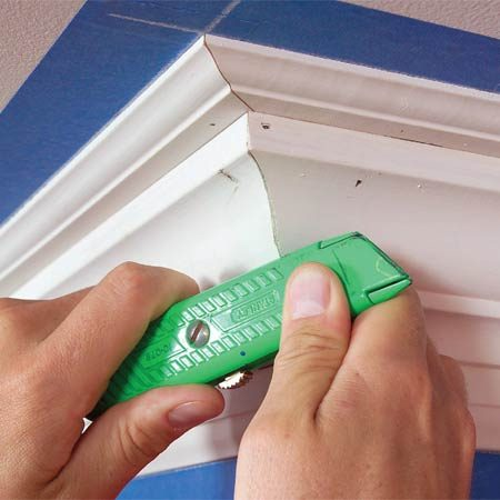 <b>Photo 19: Make small cracks disappear</b></br> Erase small cracks in outside corner joints by rubbing with a utility knife handle. This crushes the wood fibers inward and closes minor gaps.