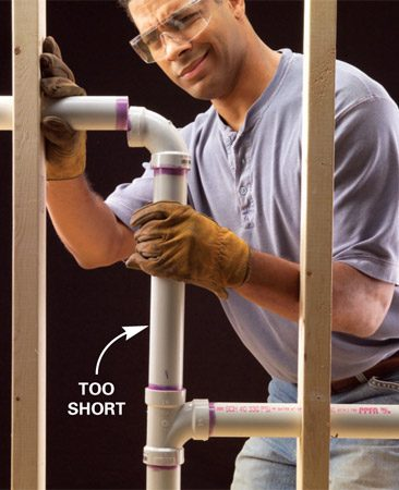 """<b>Photo 1: The problem</b></br> OOPS! The assembled pipes don't reach the predrilled hole because we dry-fit the pipes and forgot to allow extra length for """"shrinkage."""""""