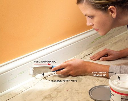 <b>Fill holes with compound.</b></br> Use a putty knife to fill all chips, holes and cracks with spackling compound.