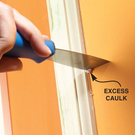 <b>Scrap excess caulk</b></br> Use a stiff putty knife to scrap away extra caulk.