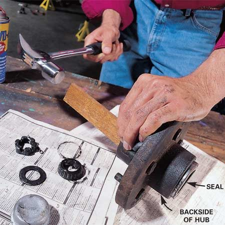 <b>Photo 5: Remove the rear bearing and seal</b></br> To remove the rear bearing and seal, tap along the rim of the bearing with a block of wood and a hammer. If the seal is rusted to the back of the hub, spray a little WD-40 on the back to help loosen it. If the seal is damaged, replace it. Clean all the grease from the bearings, races and seal with a brush in a small pan of kerosene. Inspect them for signs of wear and replace them if they look suspect. Once the bearings and parts are clean, spray them with brake cleaner and set them aside to dry. Wipe the spindle and the inside of the hub with a clean rag to remove all the grease, and clean them with brake cleaner as well.